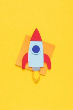 top view of flying paper rocket on yellow background, setting goals concept