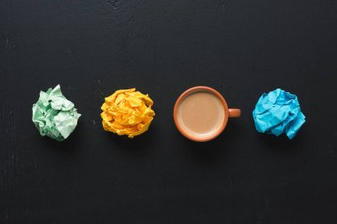 top view of colorful crumpled paper balls with coffee cup on black background