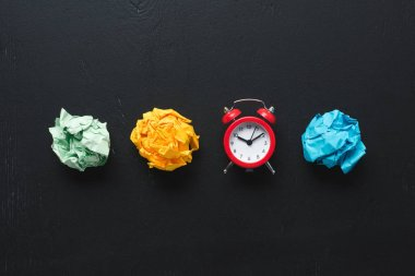 top view of colorful crumpled paper balls and clock on black background, time management concept