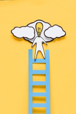 top view of cardboard man with light bulb head climbing ladder on yellow background, ideas concept