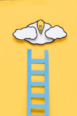 cardboard ladder with light bulb and clouds on yellow background, ideas concept