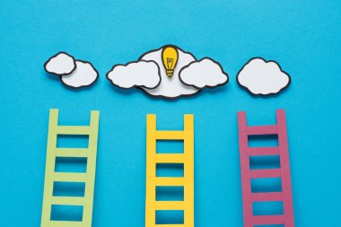 top view of cardboard ladders with light bulb and clouds on blue background, ideas concept
