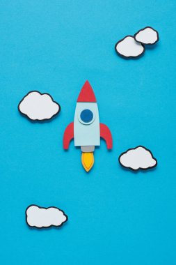 Top view of paper rocket with clouds on blue background, setting goals concept stock vector