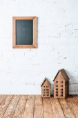 Fotografie brown blank frame on white brick wall with rustic house models on wooden table