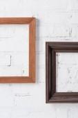 hnědá a černá prázdné rámy zavěšené na bílých cihlová zeď
