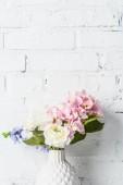 Photo bouquet  in ceramic vase near white brick wall