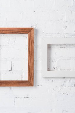 Brown and white empty frames hanging on brick wall stock vector