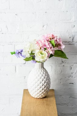 beautiful bouquet in white ceramic vase on rustic wooden shelf