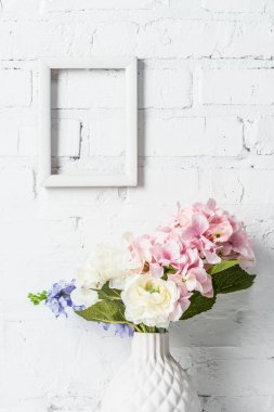 White empty frame on brick wall with flowers in ceramic vase stock vector
