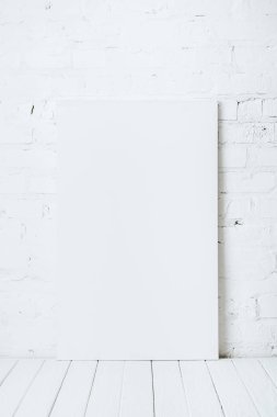 Blank placard on white wooden table near brick wall stock vector