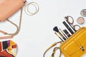 Fotografie Tašky, šátek, brýle, kosmetické štětce, rtěnky, oční stíny a náramky na bílém pozadí