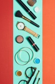 Fotografie Top view of mascara, watch, lipstick, bracelets, eyeshadow, blush, glasses and cosmetic brushes