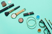Top view of mascara, watch, lipstick, bracelets, eyeshadow, blush, glasses and cosmetic brushes on turquoise background