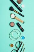 Řasenky, hodinky, rtěnky, náramky, oční stíny, tvářenky, brýle a kosmetické štětce na tyrkysové pozadí