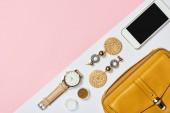 Fotografie Draufsicht auf Ohrringe, Lidschatten, Uhr, Smartphone und gelbe Tasche