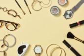 Pohled shora na hodinky, rtěnky, brýle, sluneční brýle, oční stíny, tvářenky, kosmetické štětce, náramky, náušnice a řasenky na žlutém podkladu