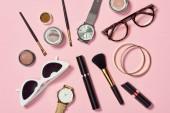 Pohled shora na hodinky, rtěnky, brýle, sluneční brýle, oční stíny, tvářenky, kosmetické štětce, náramky a řasenky