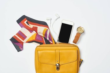 Top view of bag, smartphone, watch, scarf and earphones on white background