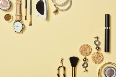 Top view of watch, sunglasses, eyeshadow, cosmetic brushes, bracelets, earrings and mascara on yellow background