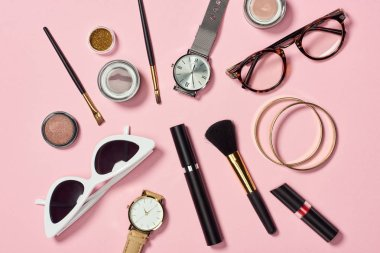 Top view of watches, lipstick, glasses, sunglasses, eyeshadow, blush, cosmetic brushes, bracelets and mascara