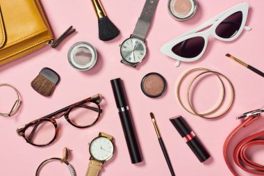 Top view of watches, lipstick, earrings, glasses, sunglasses, bag, eyeshadow, blush, belt, cosmetic brushes, bracelets and mascara