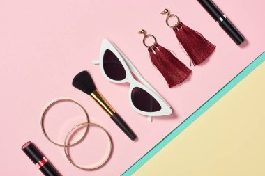 Flat lay with lipstick, bracelets, earrings, cosmetic brush, sunglasses and mascara