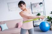 sportliche junge Frau trainiert zu Hause mit Hula-Hoop-Reifen