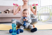 cropped shot of smiling fit mother doing exercises with dumbbells while sitting on yoga mat with her little child at home