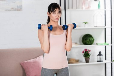 fit young woman doing exercise with dumbbells at home
