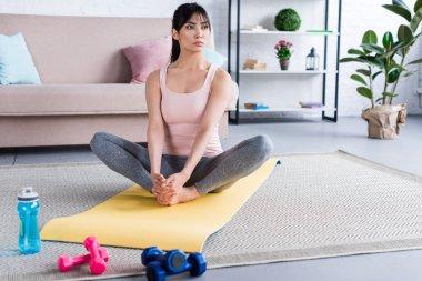 beautiful young woman practicing yoga in Bound Angle pose (Baddha Konasana) at home