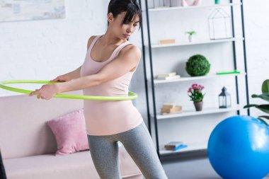 fit young woman working out with hula hoop at home
