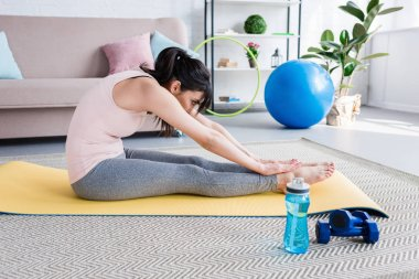 athletic young woman doing forward bend on yoga mat at home