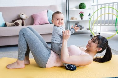 young beautiful mother lying on yoga mat with her little child at home