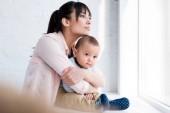 Mladá krásná matka všeobjímající své malé dítě, zatímco on sedí na parapetu a dívat se skrz okno