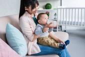 Junge glückliche Mutter füttert ihr kleines Kind mit Flasche zu Hause