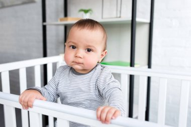 close-up portrait of cute little child in baby cot looking at camera