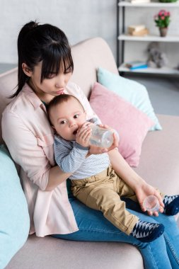 young attractive mother feeding her little child with bottle at home