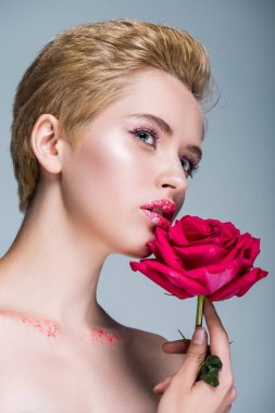 low angle view of attractive woman with glitter on lips holding red rose isolated on grey