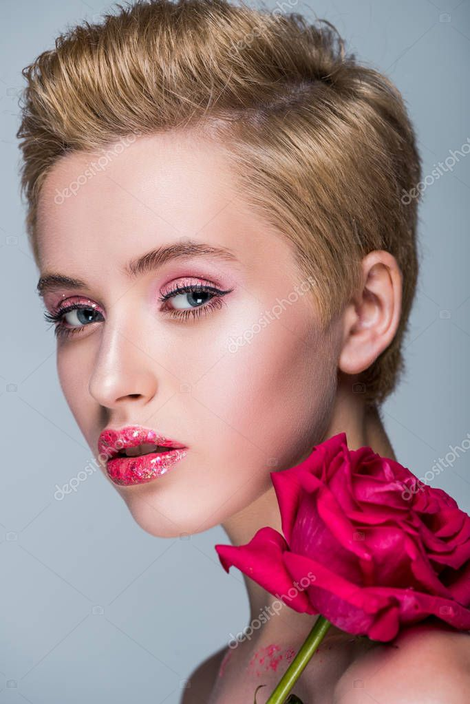 portrait of attractive woman with glitter on lips and red rose isolated on grey