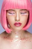 attraktive Frau mit rosa Haaren, rosa Wimpern und glitzerndem Make-up isoliert auf violett