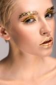 Fotografie atraktivní Kavkazský žena s zlaté třpytky na obličej při pohledu na fotoaparát