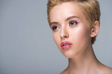attractive woman with glitter on lips and short hair looking away isolated on grey