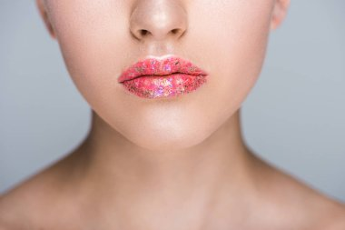 cropped image of woman with glitter on lips isolated on grey