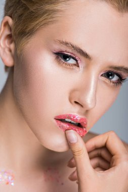 attractive woman with glittering makeup touching lips and looking at camera