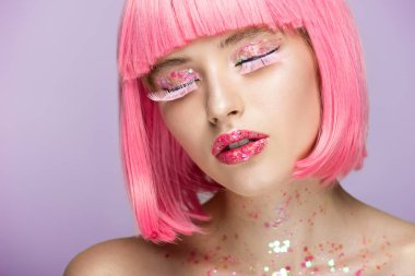 attractive woman with pink hair, glittering makeup and long eyelashes isolated on violet