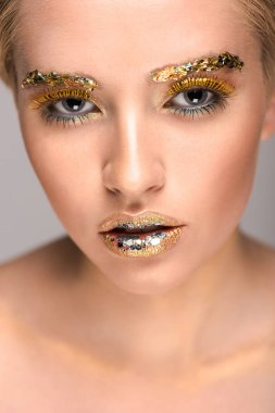 attractive woman with golden glitter on face looking at camera