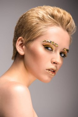 portrait of attractive woman with golden glitter on face isolated on grey