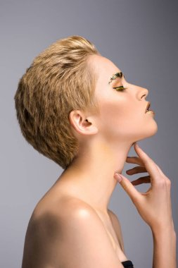 side view of attractive woman with golden glitter on face and short hair touching neck isolated on grey