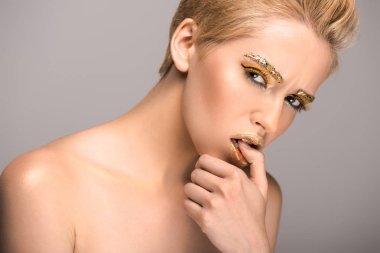 attractive woman with golden glitter on face biting thumb isolated on grey