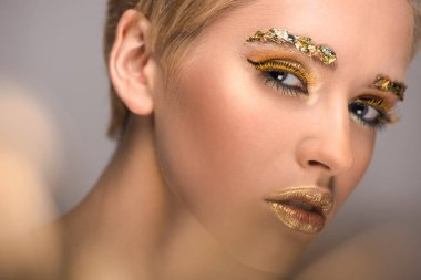 attractive woman with colored bright glitter on face looking at camera isolated on grey